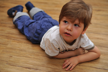 Curious small boy lying on wooden floor