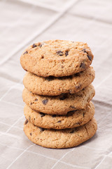 Stacked chocolate chip cookies on brown napkin.