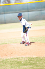Youth baseball pitcher looking.