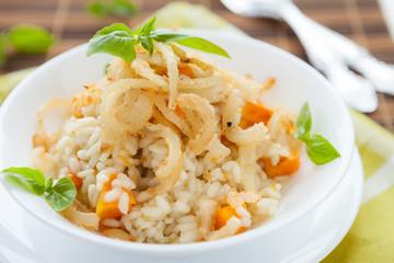 risotto with crispy onions in whie bowl