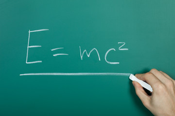 Hand writing relativity formula on blackboard