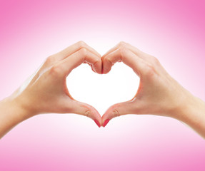 Beautiful female hands in a shape of a heart on pink
