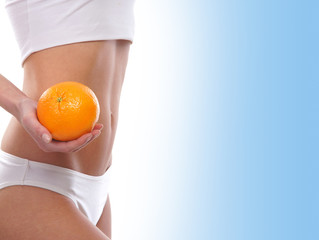 Sexy body of a young woman holding a fresh orange
