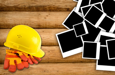 Yellow hard hat and protective gloves with grunge wall backgroun