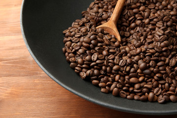 Black wok pan with coffee beans on wooden table, close up