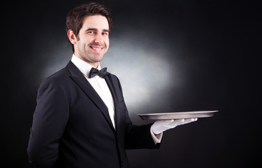 Portrait of a smiling young waiter holding an empty dish on blac