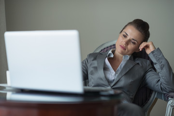 Tired business woman sitting in hotel room and looking on laptop