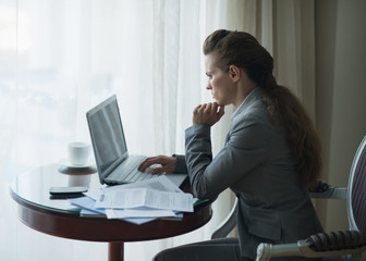 Thoughtful business woman working in hotel room