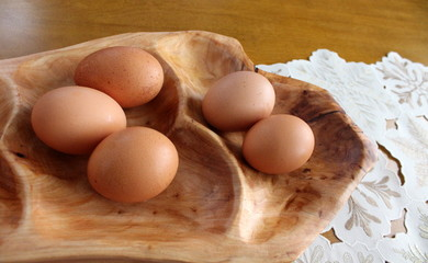 Fresh eggs on carved wood platter