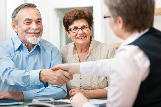 senior couple smiling while shaking hand with financial advisor