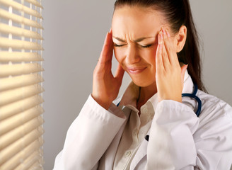 Female doctor with head pain standing near window