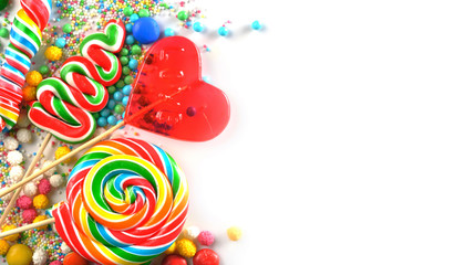 Mixed colorful candies and lollipops on white