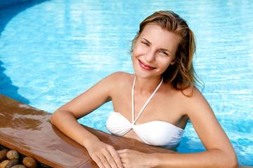 Beautiful young woman posing by the pool in tropical resort