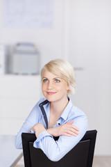 lächelnde blonde frau am arbeitsplatz