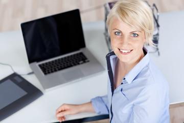 lächelnde blonde frau am schreibtisch