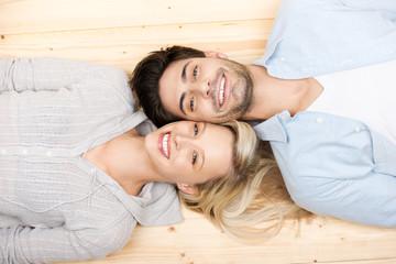 lächelndes paar liegt auf dem boden