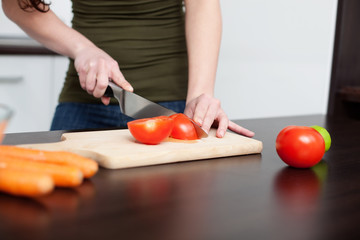 Food preparation. Woman cutting red tomato