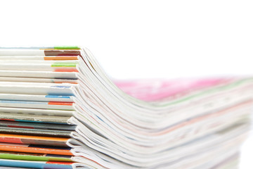 A stack of magazines on a white background. Close-up.