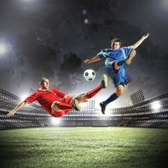 Poster Soccer ball two football players striking the ball