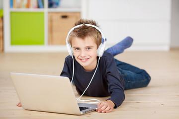 schulkind mit laptop und kopfhörern