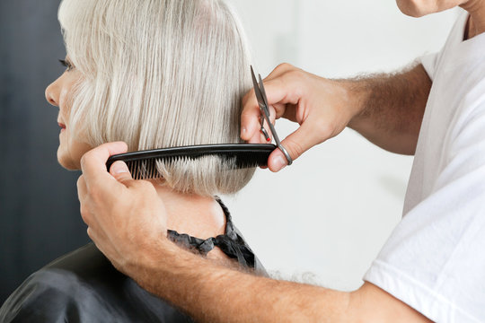 Hairstylist Measuring Hair Length Before Haircut