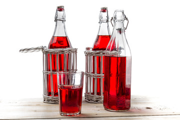 Vintage bottles with red juice on white background