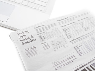 White laptop and the stock market paper. Isolated on a white bac