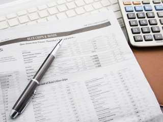 Pen and calculator on business paper or newspaper