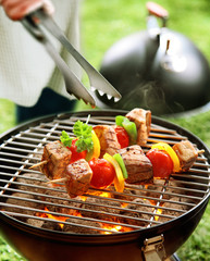 Person turning kebabs on a barbecue