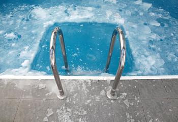 Steps in the frozen blue pool ice-hole