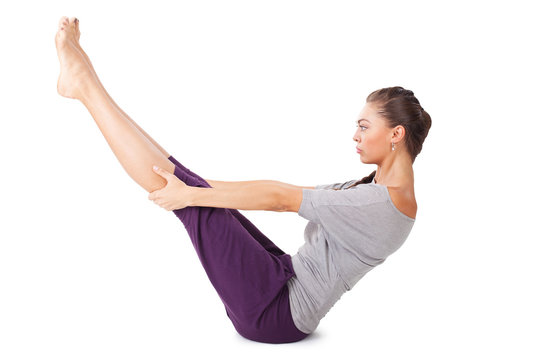 Young woman doing yoga exercise Full Boat Pose