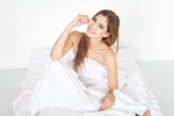 Beautiful happy young woman sitting on bed