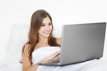 beautiful young woman with laptop on bed