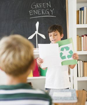 Hispanic boy reading recycling report in classroom