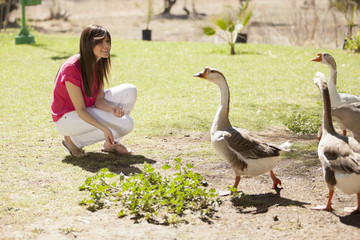 Cute young woman hanging out and feeding some ducks in a farm