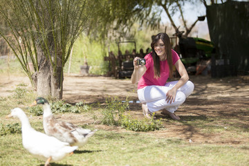 Cute girl taking some pictures of ducks in a  farm