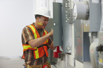 Caucasian electrician repairing fuse box