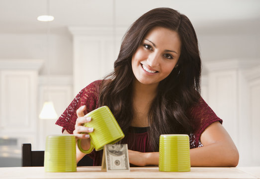 Mixed race woman finding money underneath cup