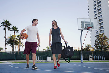 Caucasian men walking on basketball court
