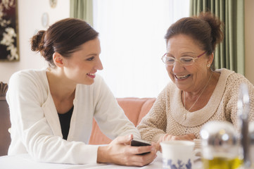 Hispanic woman showing cell phone to grandmother