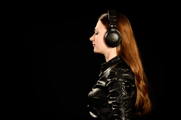 Attractive young girl with big headphones on black background