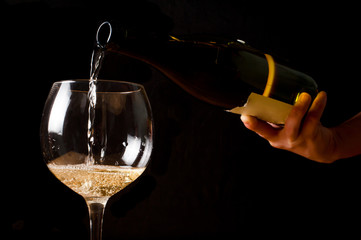pouring white wine into a wineglass on black background