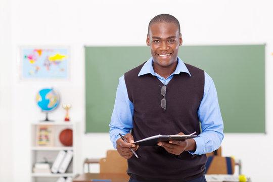 male teacher holding a clipboard