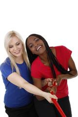 Weiße und schwarze Frau ziehen gemeinsam an einem Seil