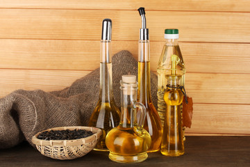 Different types of oil with sunflower seeds on wooden