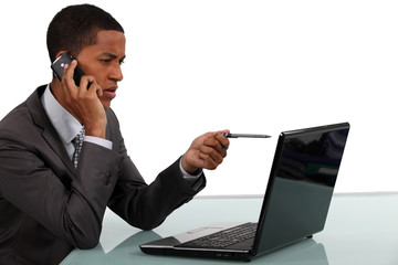 businessman looking at his laptop and talking on the phone