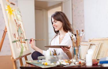 woman paints landscape on canvas