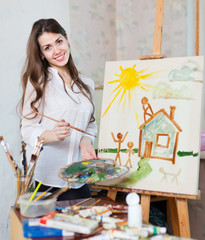 Happy young woman paints home