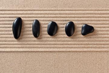 Five black pebbles on raked sand