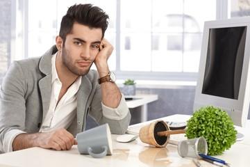 Desperate businessman sitting at desk in disorder